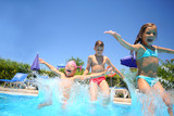 Two little girls and boy fun jumping into swimming pool