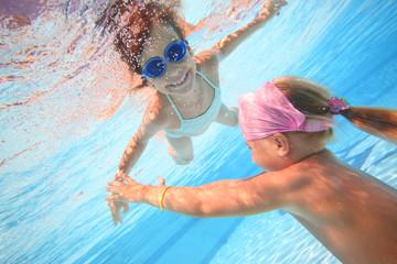 Two little girls swim underwater in the pool