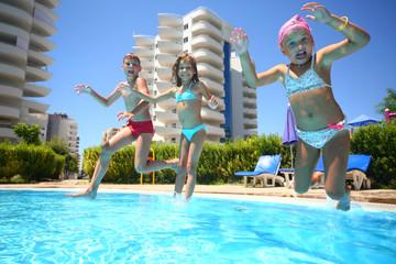 kids having fun jumping into the water swimming pool