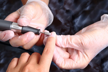 master uses an machine to remove cuticle during manicure