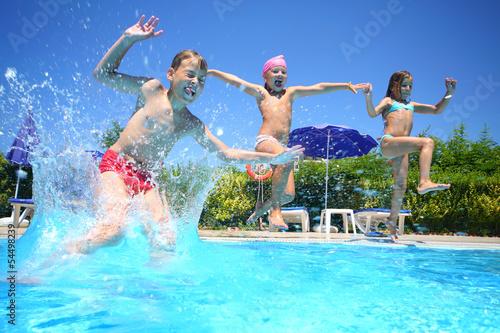 Leinwanddruck Bild Two little girls and boy fun jumping into swimming pool
