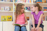 Two girls reading a book in library and laugh