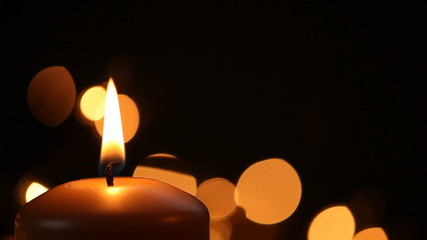 Igniting of candle on black background with copy space