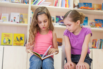 little girls are concentrated in library reading book