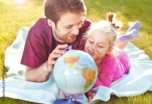 Father and daughter playing globe in the garden