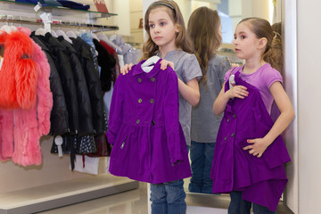 Two little cute girls near mirror try on clothe