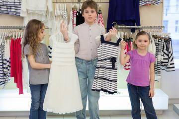 boy helps cute girls to choose dress in shop