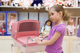 Girl in toy store with many dolls purchased buggy