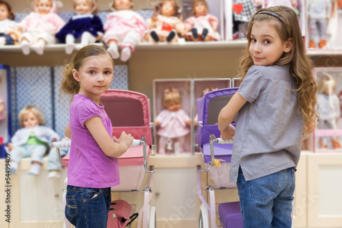 Two girls in toy store with rows of dolls  purchased buggy