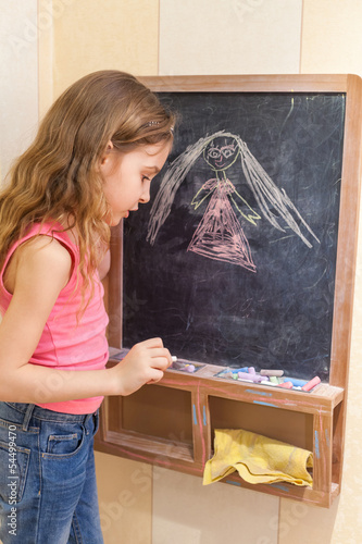 Little girl draw with chalk on blackboard