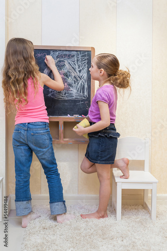 Two little girls in the playroom paint on blackboard