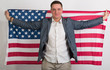 man in stylish clothing with American flag behind him