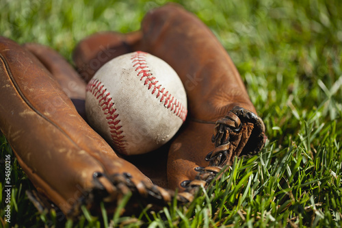 Vintage baseball mitt with an old ball in the grass