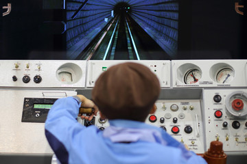 Man on simulator control panel subway car