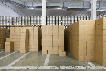 Large warehouse with beer kegs and boxes in stock brewery
