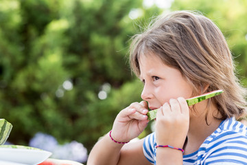 Girl eating watermelon outdoors
