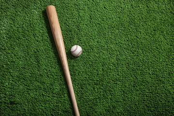 Baseball and bat on green turf viewed from above