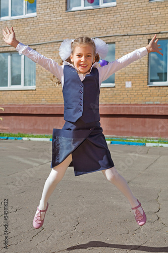 Happy little schoolgirl jumping raising his hands up