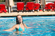 The beautiful girl floating in the pool and smiling