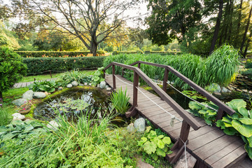 A beautiful green park with trees, flowers and a pond