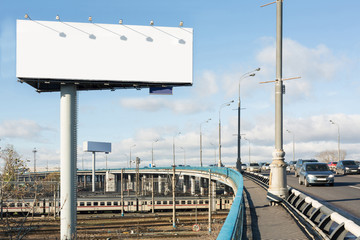 Cars driving on bridge over the railway past billboard