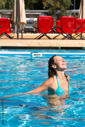 Beautiful girl with with eyes closed floating in pool
