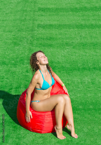 Beautiful girl sits on a soft red pufe with eyes closed