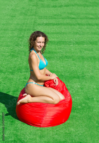 Beautiful girl sits on a soft red pufe on green grass
