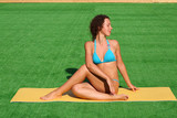 Beautiful girl doing yoga on a mat on the grass
