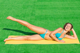 Beautiful girl doing fitness on a mat on the grass