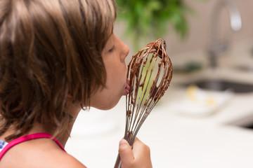 Little girl licking chocolate
