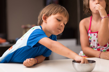 Little boy taking candy from a bowl