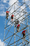 Workers working on scaffolding against a blue sky
