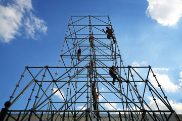 Workers working on tall scaffolding against a blue sky