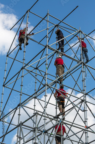 Workers make a work on scaffolding against a blue sky