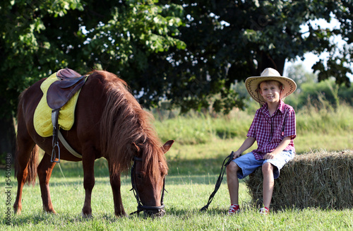 boy with cowboy hat and pony horse on farm