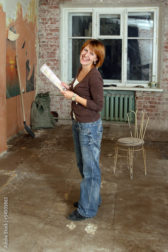 The smiling women with property deed in unrepair apartment