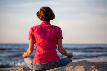 Woman meditating at seaside