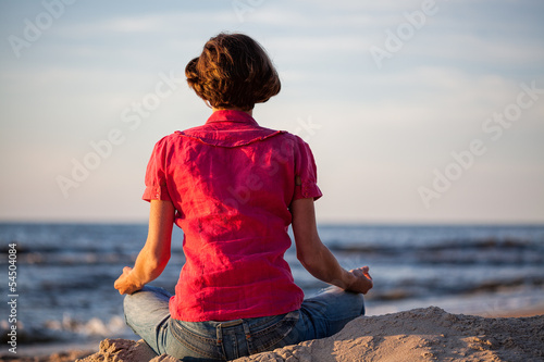 Woman meditating at seaside