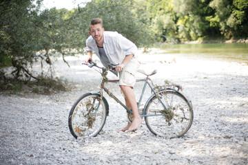 junger Mann mit altem Fahrrad
