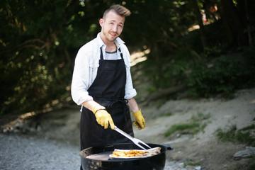 junger Mann beim Grillen