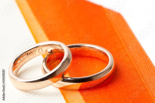 gold wedding rings near orange ribbon