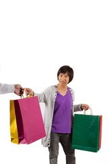 Shopping woman giving shopping bags to another person on white b