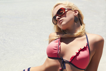 Beautiful blond woman in sunglasses on paradise beach
