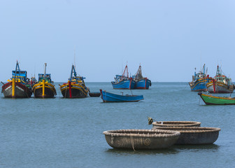A few fishing vessels float on the South China sea in front of M