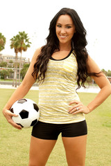 Pretty athletic woman with football in her hand