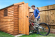 canvas print picture - Man pushing his bike into a shed for storage