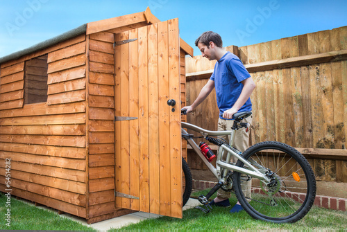 canvas print picture Man pushing his bike into a shed for storage