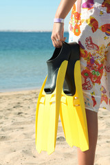 Woman on beach with pair of fins
