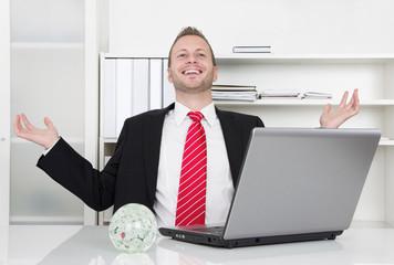 Junger Unternehmer freut sich im Büro über seinen Erfolg